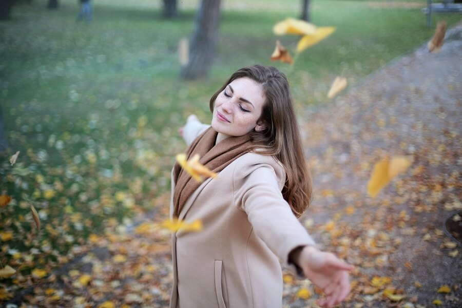Woman holds arms out while leaves fall