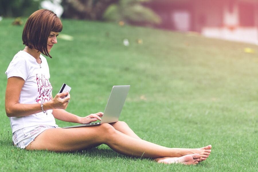 Woman sits on grass with laptop and holding credit card