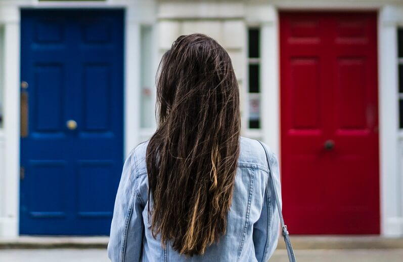 Woman stands in front of a blue door and a red door