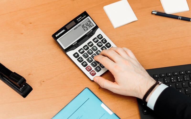 Hand typing into a calculator