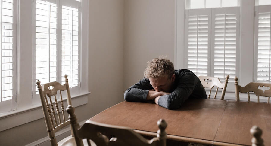 Stressed man sitting at dining table