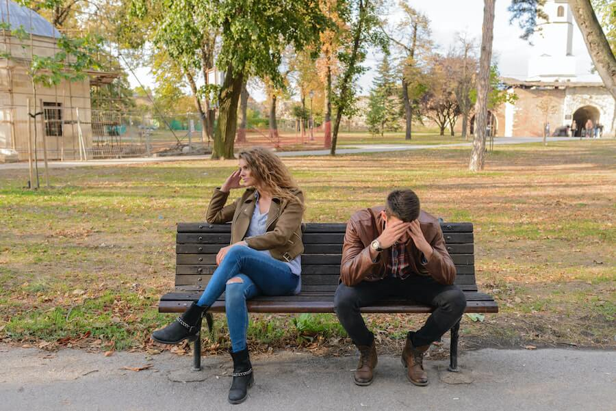 Frustrated man and woman sitting on a bench in a park