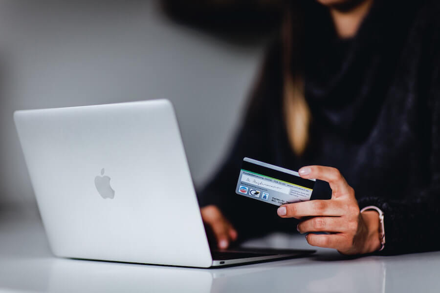 Woman holding a credit card in front of a laptop
