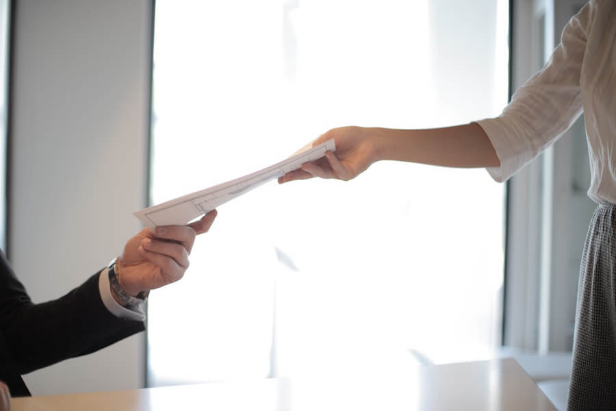 Woman handing man stack of papers